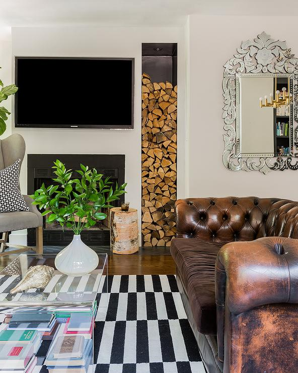 TV above fireplace with storage for wood in living room with tufted leather sofa