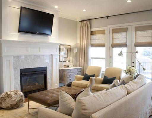tv high above the fireplace in this cream living room
