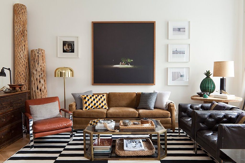 Living room with mix of furniture in different styles, colour and finishes and large area rug in bold stripes