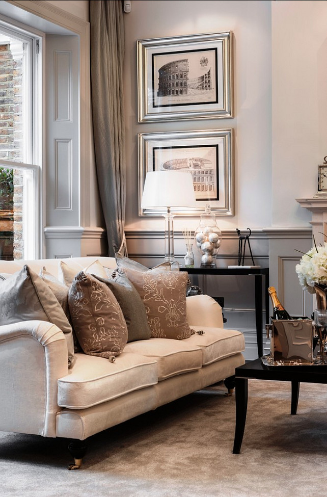 English cream sofa in traditional setting with large throw cushions and pale grey walls