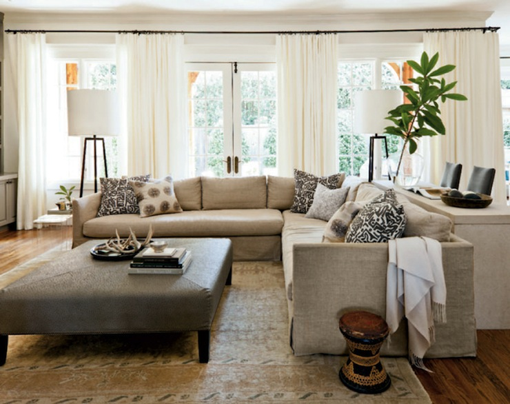 Sectional sofa with comfortable back cushions in large casual living room with floor lamps and ottoman table