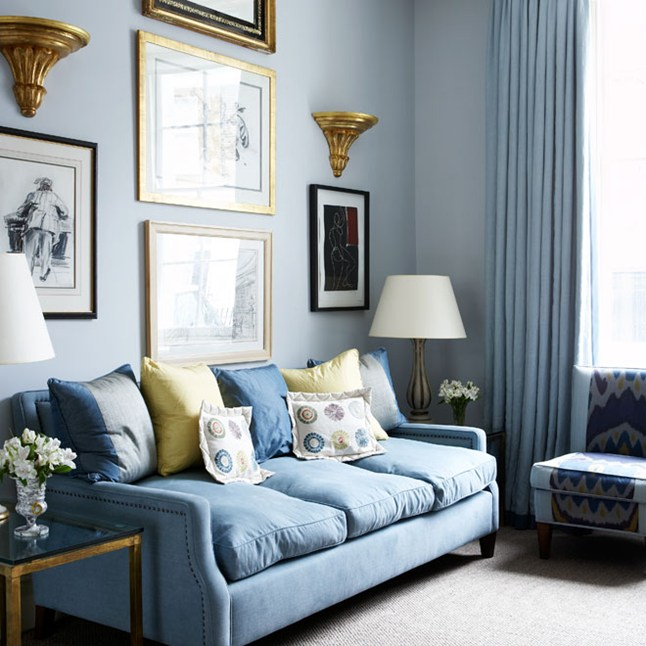 Pale blue sofa with gold accents and yellow cushions ainst blue wall and high ceiling