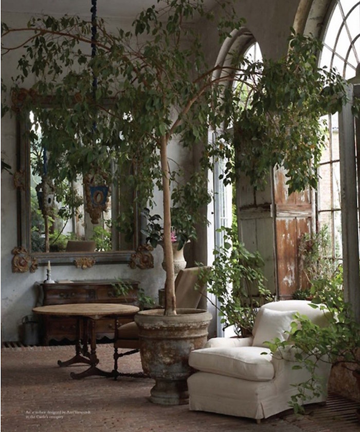garden room with potted plants and armchair