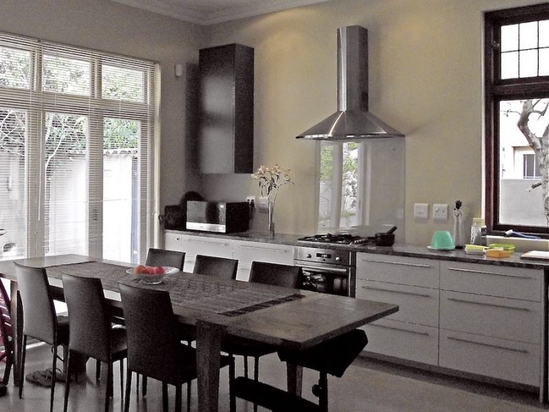 Contemporary kitchen with glass backsplash and large dining table